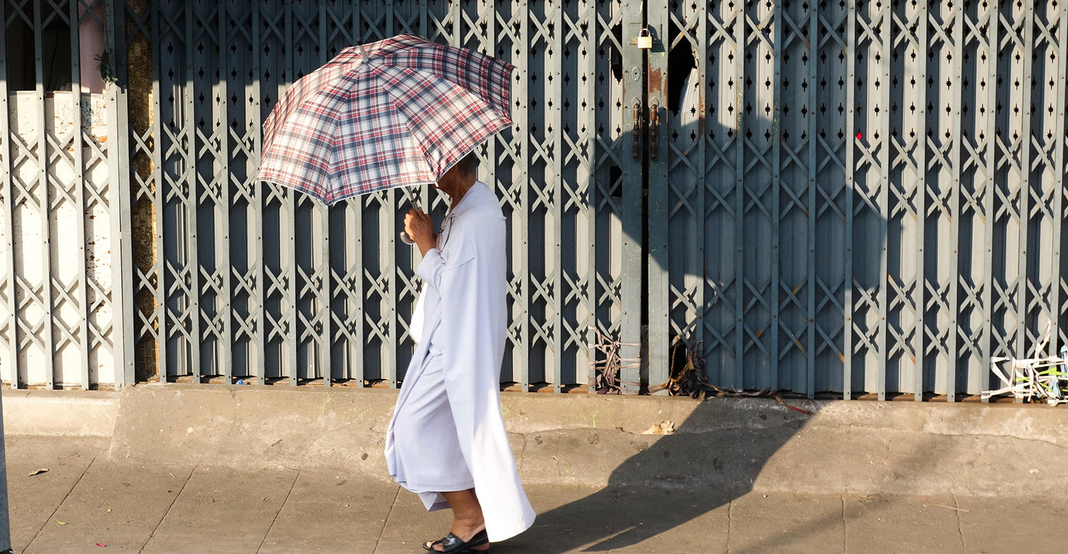Buddhist Man with umbrella against sun walking in street, Bangkok, Thailand, Southeast Asia.